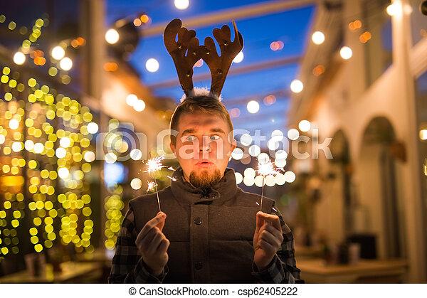 Gente, vacaciones y el concepto de Navidad - joven gracioso vestido de ciervo de Navidad con bengals light al aire libre - csp62405222