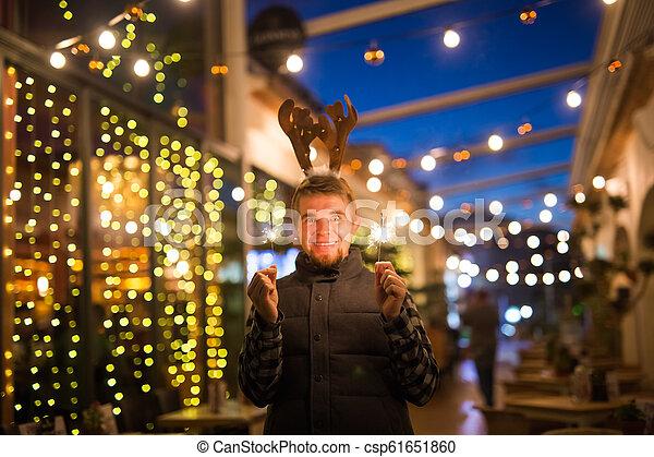 Gente, vacaciones y el concepto de Navidad - joven gracioso vestido de ciervo de Navidad con bengals light al aire libre - csp61651860
