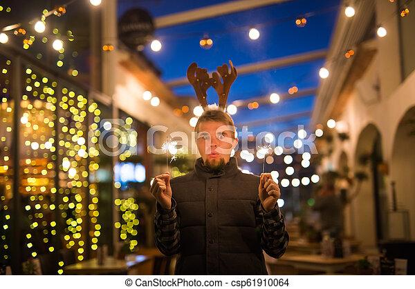 Gente, vacaciones y el concepto de Navidad - joven gracioso vestido de ciervo de Navidad con bengals light al aire libre - csp61910064