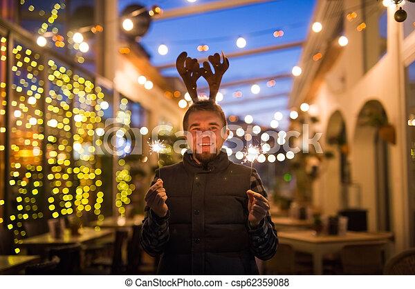 Gente, vacaciones y el concepto de Navidad - joven gracioso vestido de ciervo de Navidad con bengals light al aire libre - csp62359088