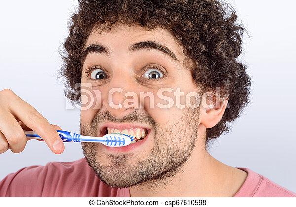 Un joven gracioso lavándose los dientes. - csp67610598