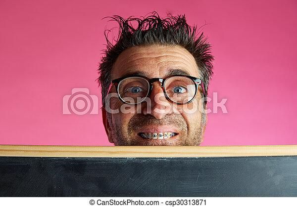 Hombre nerd loco detrás de la pizarra gesto gracioso - csp30313871