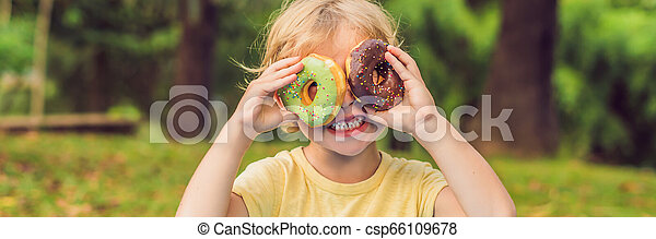 Chico gracioso con donas. El niño se está divirtiendo con donas. Comida sabrosa para niños. Tiempo feliz al aire libre con comida dulce, largo formato - csp66109678