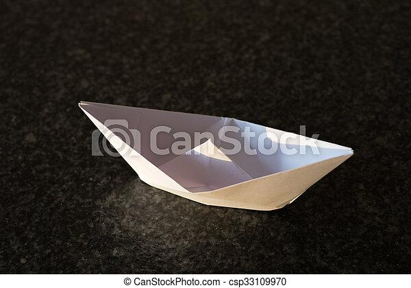 Un barco de papel blanco doblado en un fondo negro - csp33109970