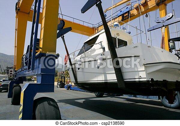Dock crane elevating a fishing boat - csp2138590
