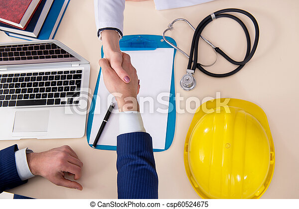 Doctor and manager agreeing industrial insurance coverage - csp60524675