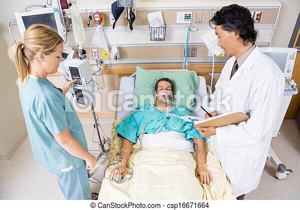 Doctor And Nurse Examining Critical Patient - csp16671664