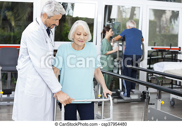 Doctor Assisting Senior Female Patient With Walker In Fitness St - csp37954480