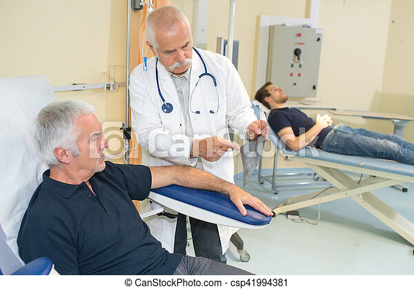 doctor examining his patient arm in medical office - csp41994381