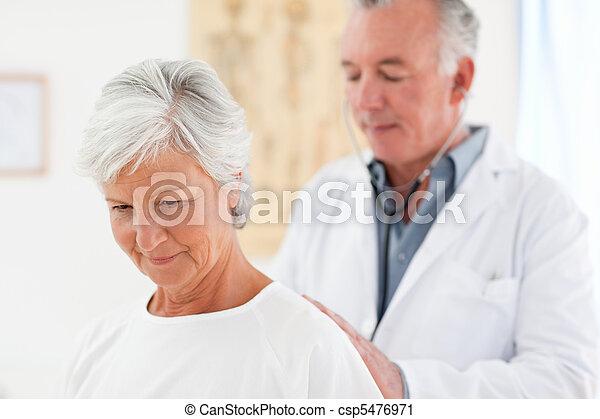 Doctor examining his patient - csp5476971
