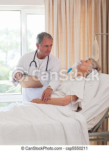 Doctor examining his patient - csp5550211