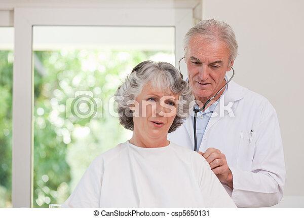 Doctor examining his  patient - csp5650131