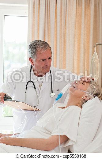 Doctor examining his patient - csp5550168