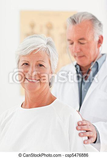 Doctor examining his patient - csp5476886