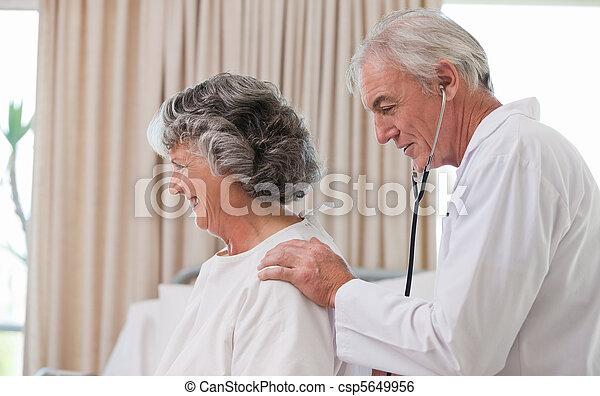 Doctor examining his  patient - csp5649956