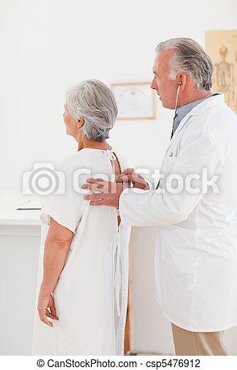 Doctor examining his patient - csp5476912