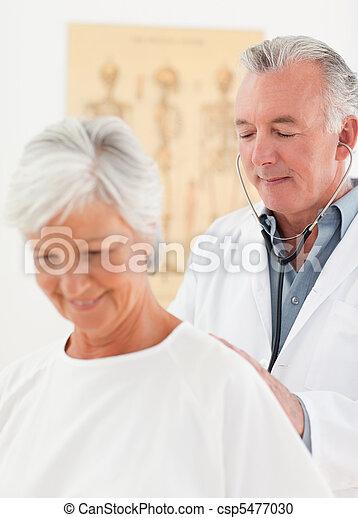 Doctor examining his patient - csp5477030