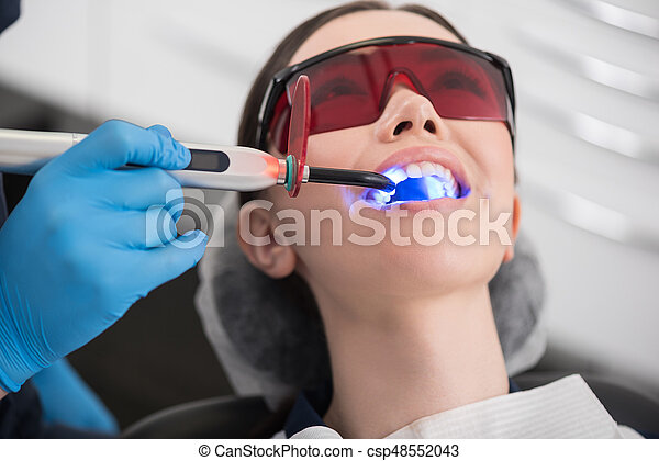 Doctor examining mouth of outgoing female - csp48552043