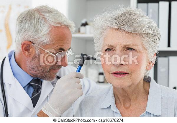 Doctor examining senior patient's ear - csp18678274
