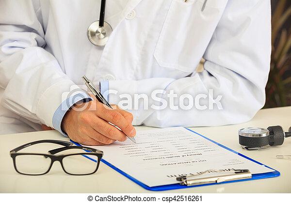 Doctor filling a medical form on his desk
