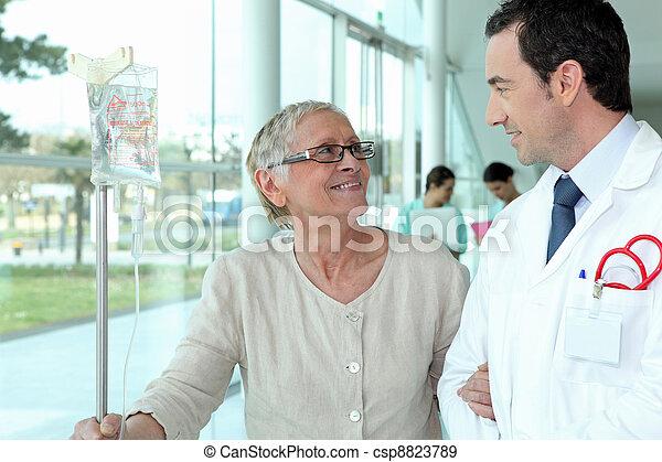 Doctor helping elderly patient in hall - csp8823789