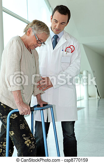 Doctor helping elderly patient with walking frame - csp8770159