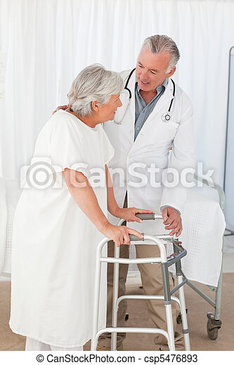 Doctor helping his patient to walk - csp5476893