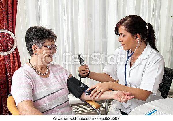 Doctor measuring patient blood pressure - csp3926587