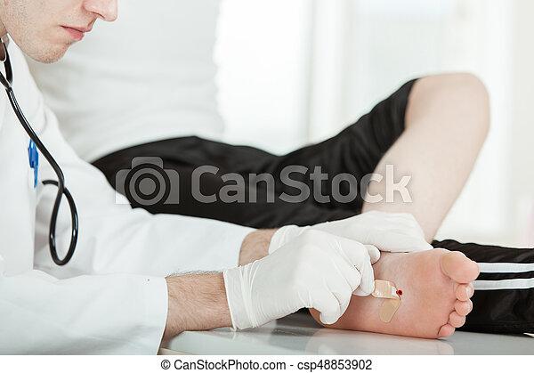Doctor Peeling Bandage Off Patient Foot Injury - csp48853902