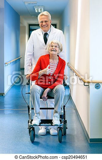 Doctor pushing an elderly woman in a wheelchair. - csp20494651