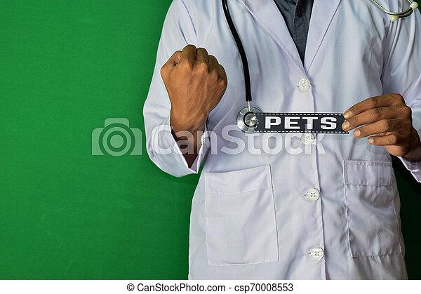 Un doctor de pie, mantenga el texto de papel de Mascotas sobre fondo verde. Un concepto médico y de salud. - csp70008553