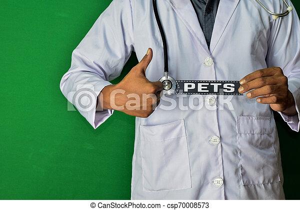 Un doctor de pie, mantenga el texto de papel de Mascotas sobre fondo verde. Un concepto médico y de salud. - csp70008573