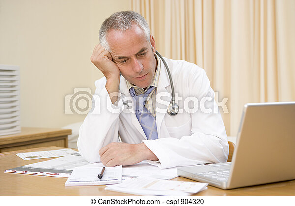 Doctor with laptop in doctor's office - csp1904320