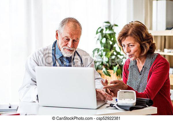 Doctor with laptop talking to a senior woman in office. - csp52922381