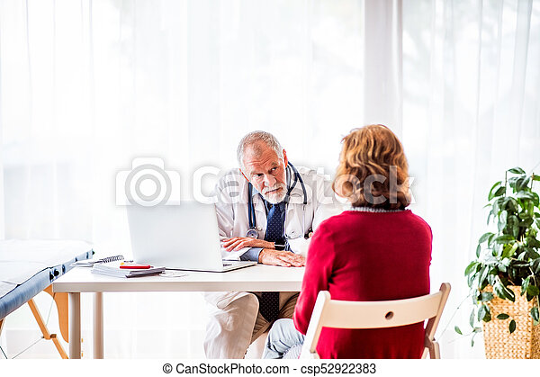 Doctor with laptop talking to a senior woman in office. - csp52922383