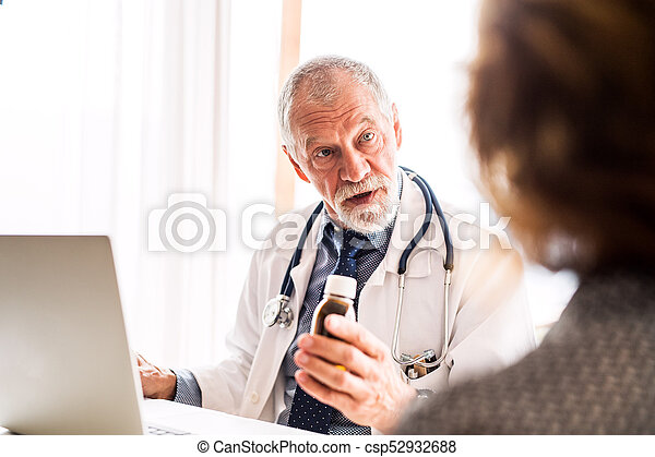 Doctor with laptop talking to a senior woman in office. - csp52932688