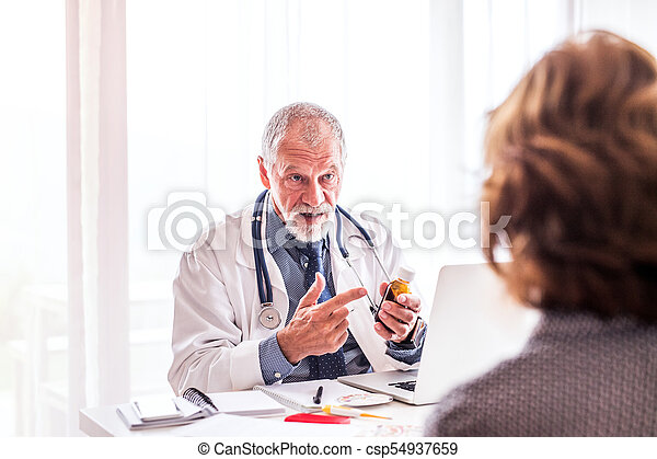 Doctor with laptop talking to a senior woman in office. - csp54937659