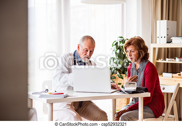Doctor with laptop talking to a senior woman in office. - csp52932321