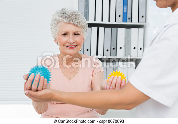 Doctor with senior patient using stress buster balls - csp18678693