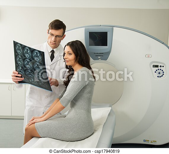 Doctor with young woman patient looking at the computed tomography results - csp17940819