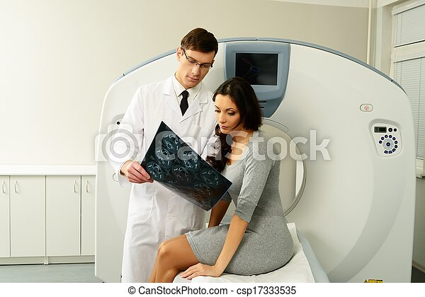 Doctor with young woman patient looking at the computed tomography results - csp17333535