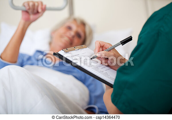 Doctor Writing On Clipboard While Looking At Patient - csp14364470