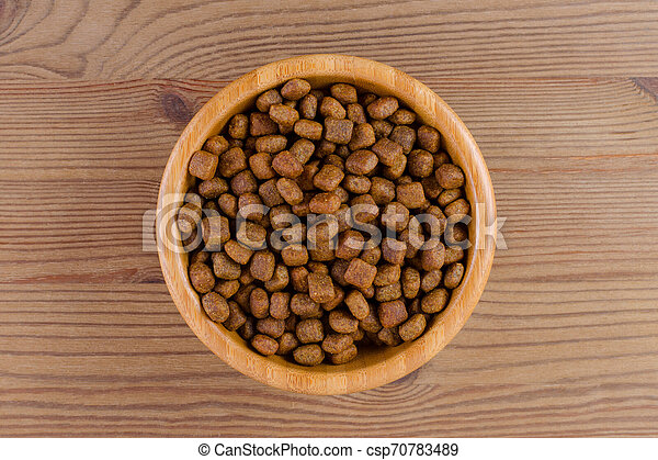 dog food in a bowl on wooden background, flat lay - csp70783489