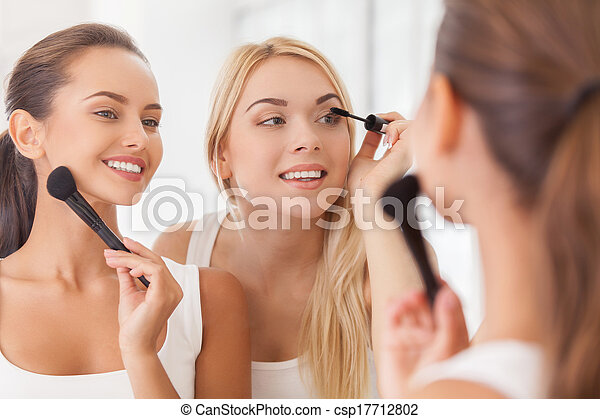 Doing make-up together. Two beautiful young women doing make-up together while looking at the mirror and smiling - csp17712802