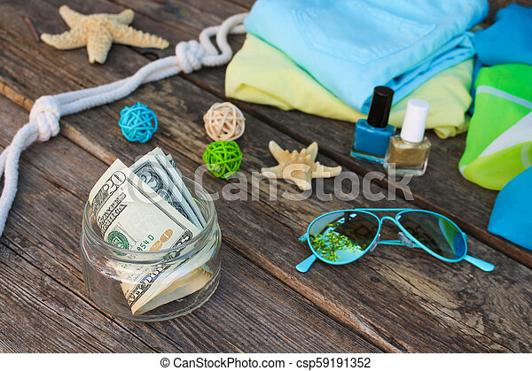 Dollars in glass jar. Concept of collecting money for journey. - csp59191352
