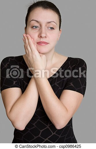 Dolor de muelas. hermosa mujer en un fondo gris.
