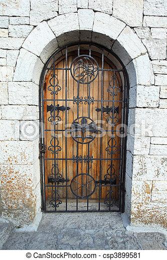 Door behind lattice in stone wall - csp3899581