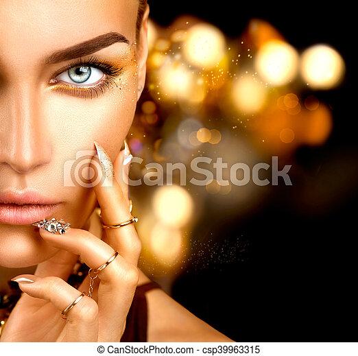Mujer de moda con maquillaje dorado, accesorios y uñas - csp39963315