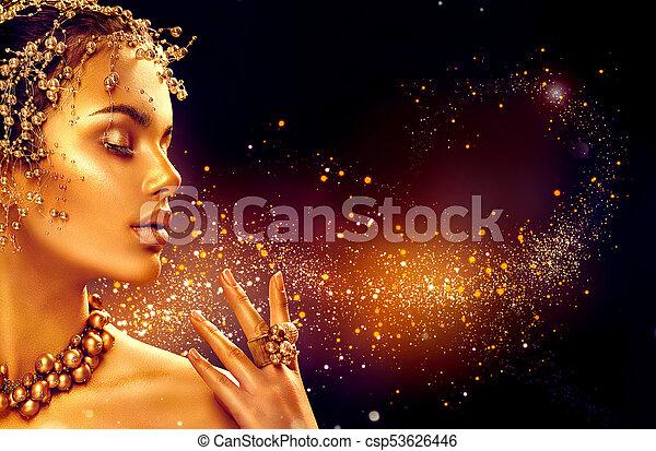 Piel de mujer de oro. Una chica modelo de belleza con maquillaje dorado, cabello y joyas en fondo negro - csp53626446