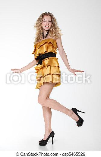 Chica feliz sonriendo con vestido dorado - csp5465526